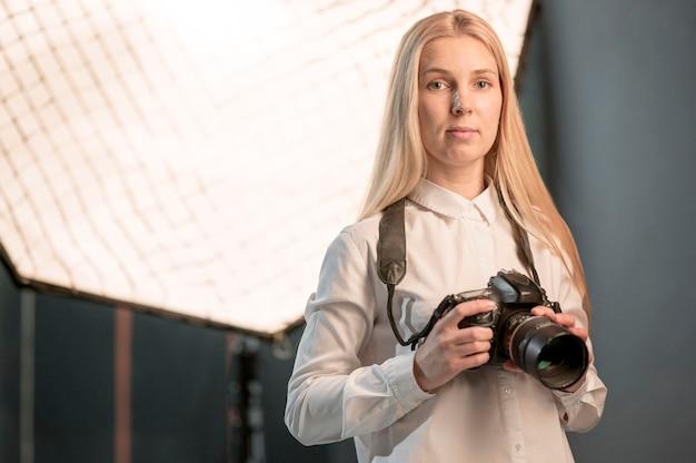 Średnio strzał śliczna blondynki dziewczyna i kamery fotografia
