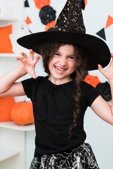 Średnio strzał śliczna mała dziewczynka z czarownica kapeluszem