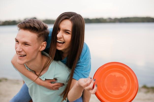 Średnio strzał śmiejących się nastolatków z frisbee