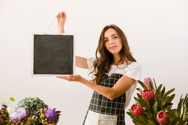 Średnio strzał smiley kwiaciarnia trzyma czarną deskę