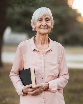 Średnio strzał smiley woman holding book