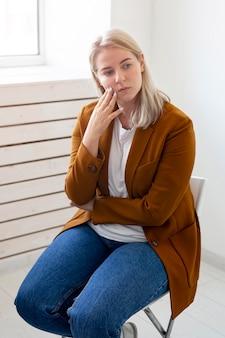Średnio strzał smutna kobieta siedzi na krześle