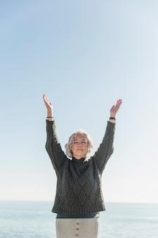 Średnio strzał stara kobieta z zamkniętymi oczami na plaży