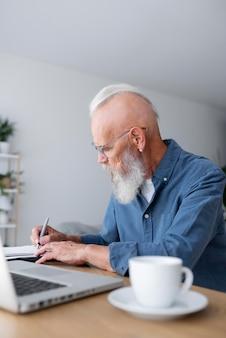Średnio strzał starszy mężczyzna robiący notatki