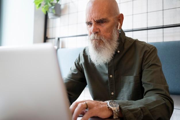 Średnio strzał starszy mężczyzna studiujący z laptopem