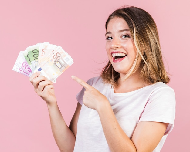 Średnio strzał szczęśliwa dziewczyna trzyma pieniądze