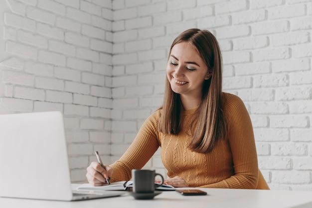 Średnio strzał szczęśliwa kobieta pisze