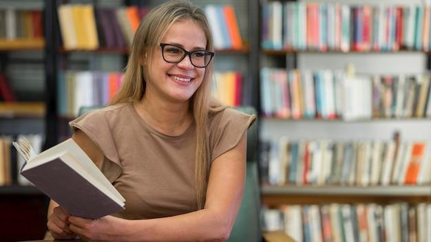 Średnio strzał szczęśliwa kobieta trzyma książkę