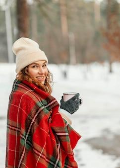 Średnio strzał szczęśliwa kobieta trzyma kubek