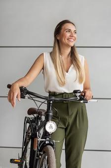 Średnio strzał szczęśliwa kobieta z rowerem