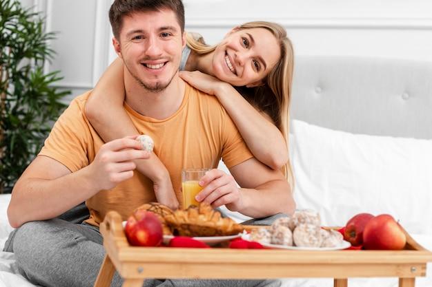 Średnio strzał szczęśliwa para ze śniadaniem w łóżku