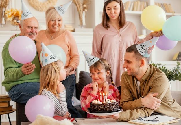 Średnio strzał szczęśliwa rodzina z ciastem