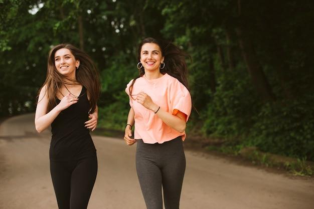 Średnio strzał szczęśliwe dziewczyny biegną razem
