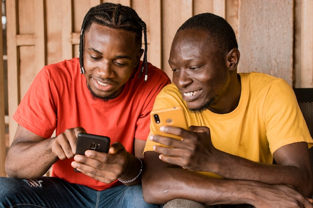Średnio strzał szczęśliwi mężczyźni ze smartfonami