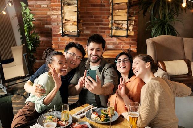 Średnio strzał szczęśliwi przyjaciele biorący selfie