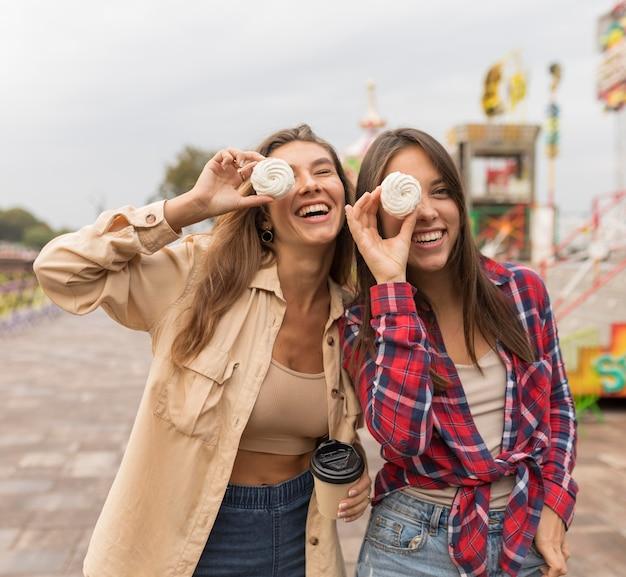Średnio strzał szczęśliwi przyjaciele pozujący ze słodyczami