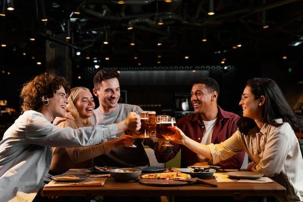 Średnio strzał szczęśliwi przyjaciele z kuflami do piwa