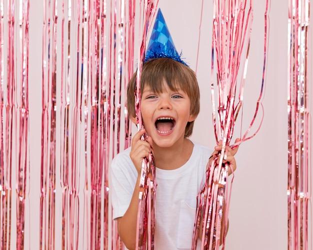 Średnio strzał szczęśliwy chłopiec na sobie niebieski kapelusz