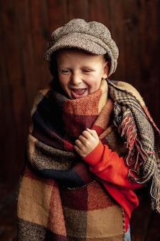 Średnio strzał szczęśliwy chłopiec z czapką i szalikiem