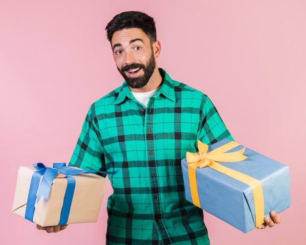 Średnio strzał szczęśliwy facet trzyma prezenty