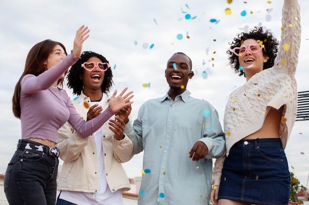 Średnio strzał szczęśliwych ludzi bawiących się konfetti