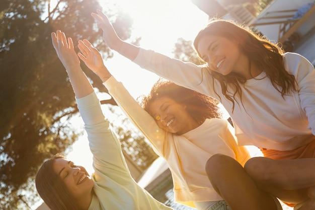 Średnio strzał szczęśliwych przyjaciół na zewnątrz