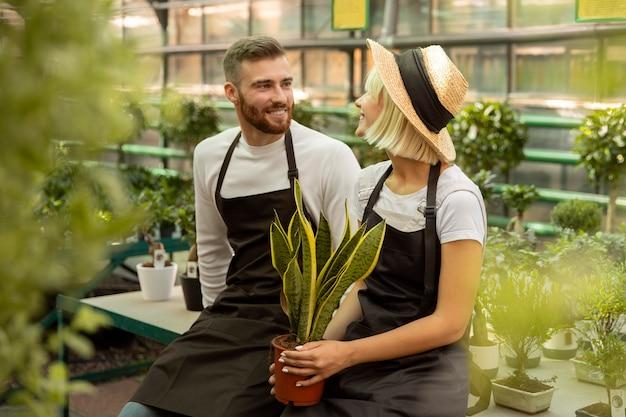 Średnio strzał uśmiechnięci ludzie z rośliną