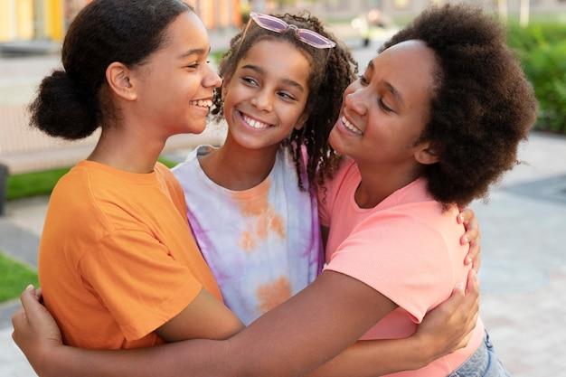 Średnio strzał uśmiechnięci przyjaciele przytulający się