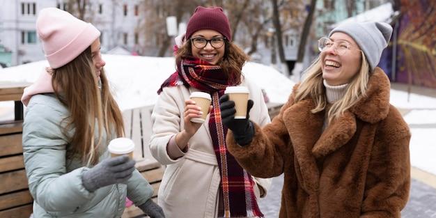 Średnio strzał uśmiechnięci przyjaciele z filiżankami do kawy