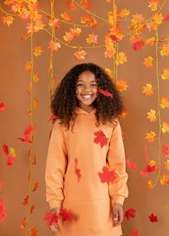 Średnio strzał uśmiechnięta dziewczyna pozuje z liśćmi
