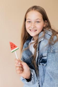Średnio strzał uśmiechnięta dziewczyna pozuje z lodami