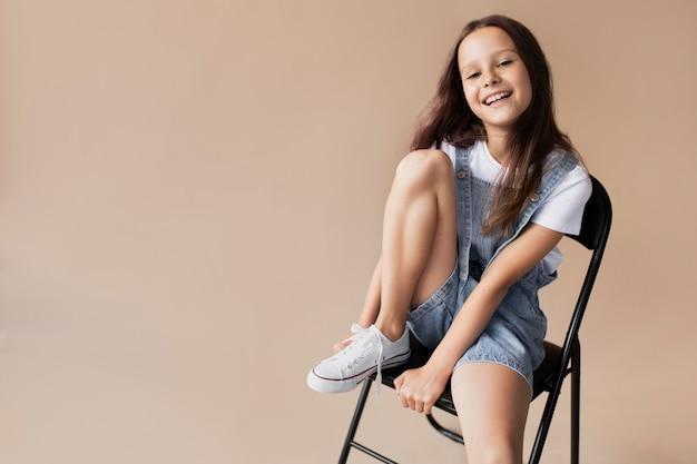 Średnio strzał uśmiechnięta dziewczyna siedzi na krześle
