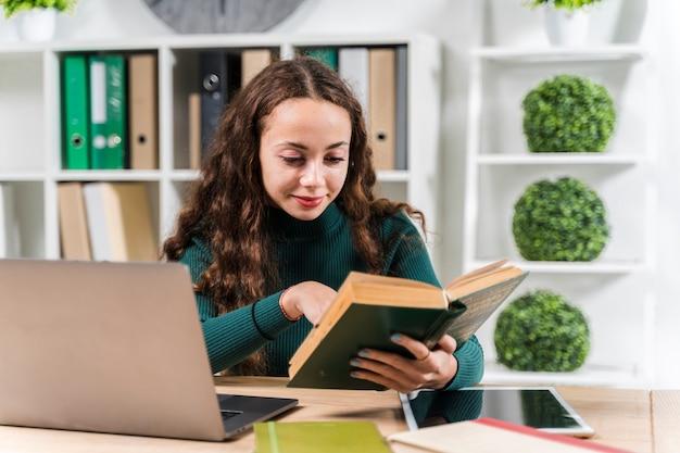 Średnio strzał uśmiechnięta dziewczyna studiuje ze słownikiem