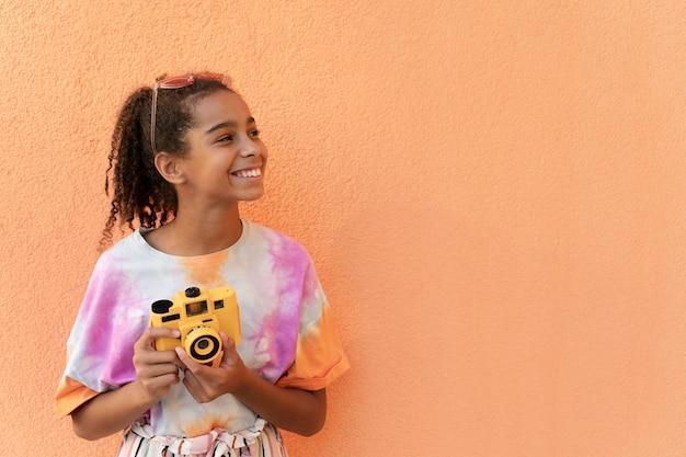 Średnio strzał uśmiechnięta dziewczyna trzyma aparat