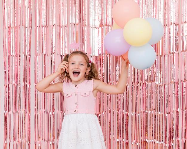 Średnio strzał uśmiechnięta dziewczyna trzyma balony