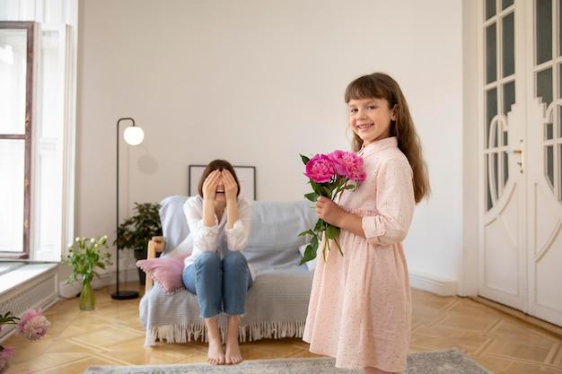 Średnio strzał uśmiechnięta dziewczyna trzyma kwiaty