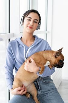 Średnio strzał uśmiechnięta dziewczyna trzyma psa