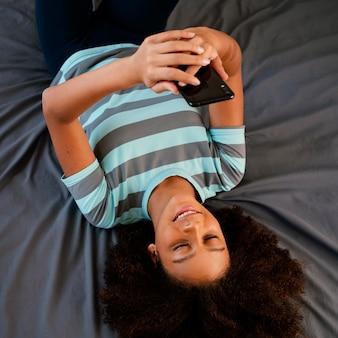 Średnio strzał uśmiechnięta dziewczyna z smartphone