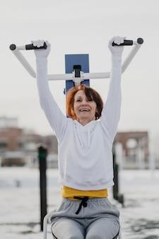 Średnio strzał uśmiechnięta kobieta ćwiczeń