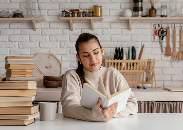 Średnio strzał uśmiechnięta kobieta czytania w pomieszczeniu