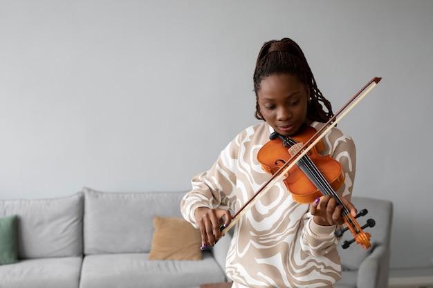 Średnio strzał uśmiechnięta kobieta grająca na skrzypcach