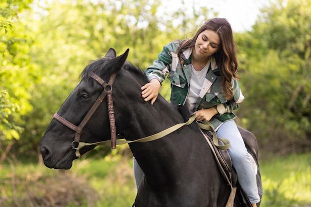 Średnio strzał uśmiechnięta kobieta jedzie na koniu