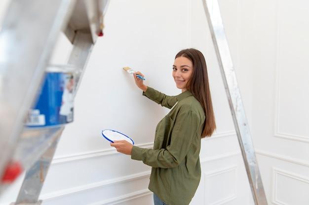 Średnio strzał uśmiechnięta kobieta malująca ścianę