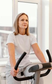 Średnio strzał uśmiechnięta kobieta na rowerze spin