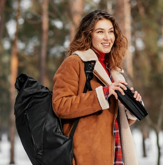 Średnio strzał uśmiechnięta kobieta niosąca plecak