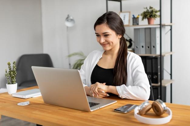 Średnio strzał uśmiechnięta kobieta robi pracę