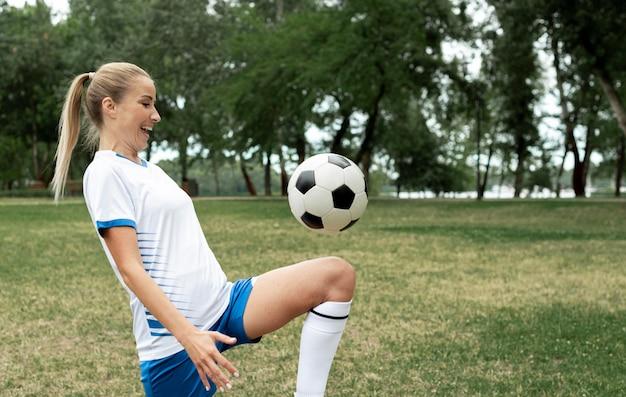 Średnio strzał uśmiechnięta kobieta szkolenia z piłką