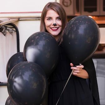 Średnio strzał uśmiechnięta kobieta trzyma balony