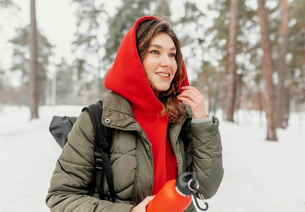 Średnio strzał uśmiechnięta kobieta trzyma butelkę