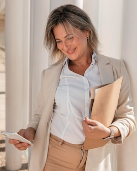 Średnio strzał uśmiechnięta kobieta trzymając telefon